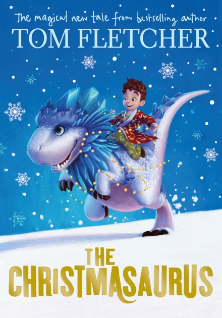 Book cover of 'The Christmasaurus'. Cover shows a boy riding the christmasaurus while snowflakes fall to the ground around them.