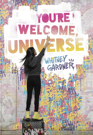 Book cover of 'You're Welcome, Universe'. Cover shows a person stood on a box of old cans on a street, spray painting the book's title amongst other, colourful, street art.